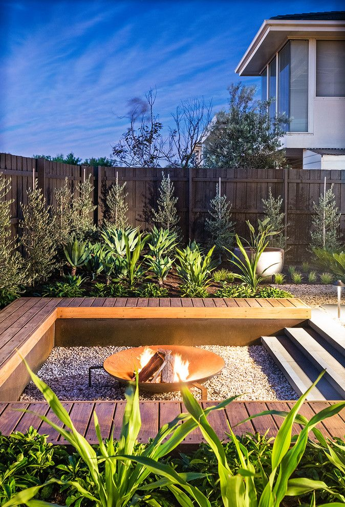 backyard with fire pit in the middle surrounded b square seating area that is surrounded by planting area