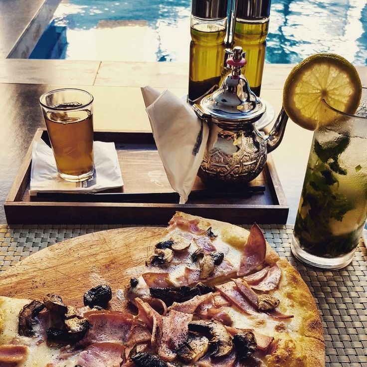 """Almost everything about this meal makes little sense in a predominantly Muslim country: a very non- halal pizza a very boozy #mojito   all served poolside while """"turn down for what"""" cranks at >120 decibels.  Only the tea seems to be SoP for #marrakesh #foodporn"""