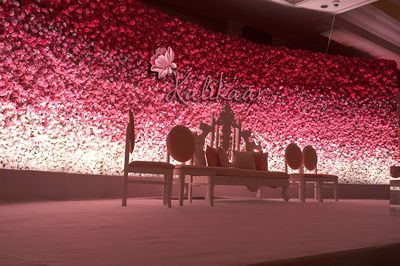 gradient, floral wall, red and pink, shaded, stage backdrop, roses, white furniture, white couple seat
