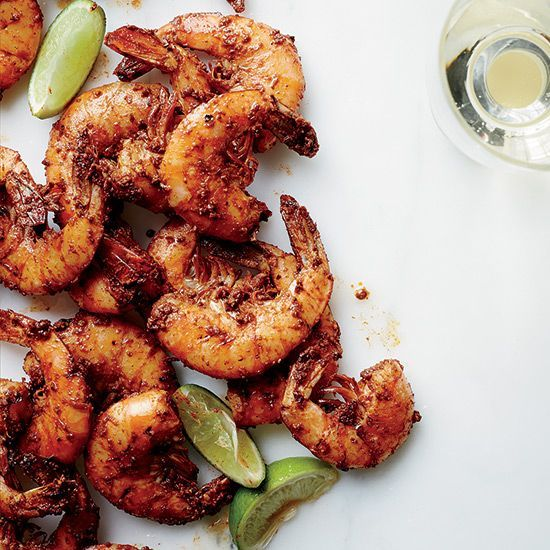 These messy and delicious shell-on shrimp are coated in a brick-red sauce made of crushed pepper and spices, then grilled and served with lime wedges.
