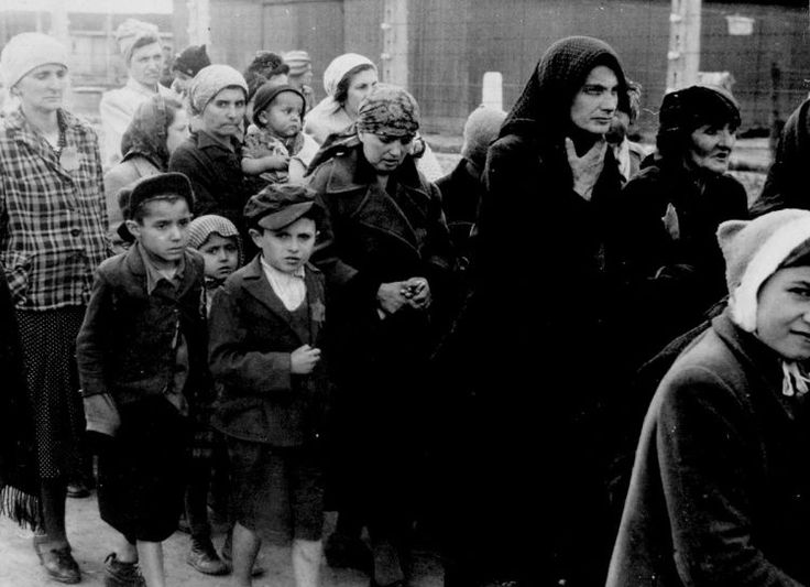 """Auschwitz Jewish women and children forced to walk towards the gas chambers. On the platform, some railroad cars are still waiting. No memory of the men, women, and children that were deemed """"valueless"""" upon their arrival remains in camp records."""