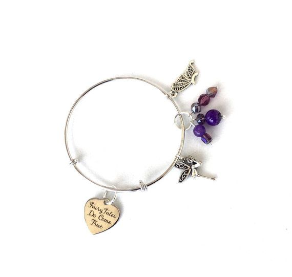 If you believe in fairytales, you will adore this beautiful fairytale inspired bangle! This bangle is rhodium plated and adjustable, making fit most. It includes a silver plated heart pendant with the words FairyTales Do Come True. I added whimsical fairy and butterfly wing charms