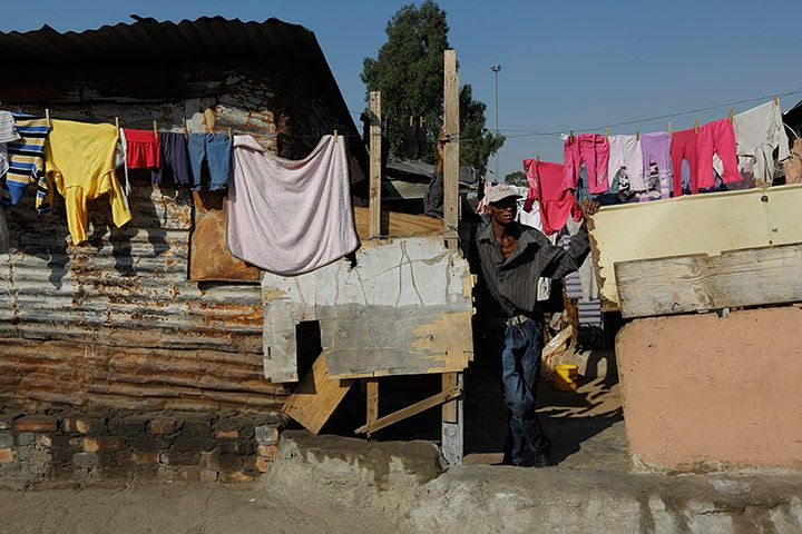 A man stands behind a washing line by homes made from corrugated iron and spare wood. Credit: Kim Ludbrook/EPA