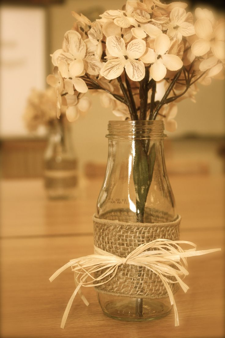 Table decorations made from Starbucks Frappucino bottles, burlap and raffia!