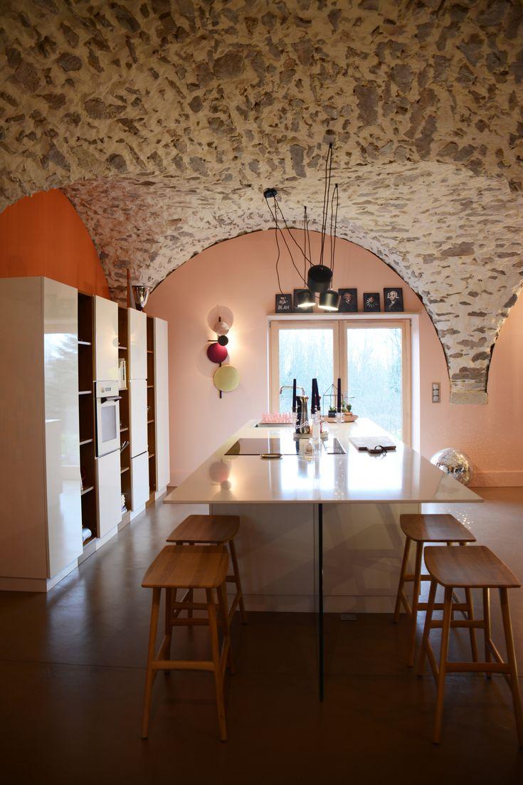 cuisine blanche et bois avec murs orange et rose et pierre. Au sol du béton ciré chocolat.