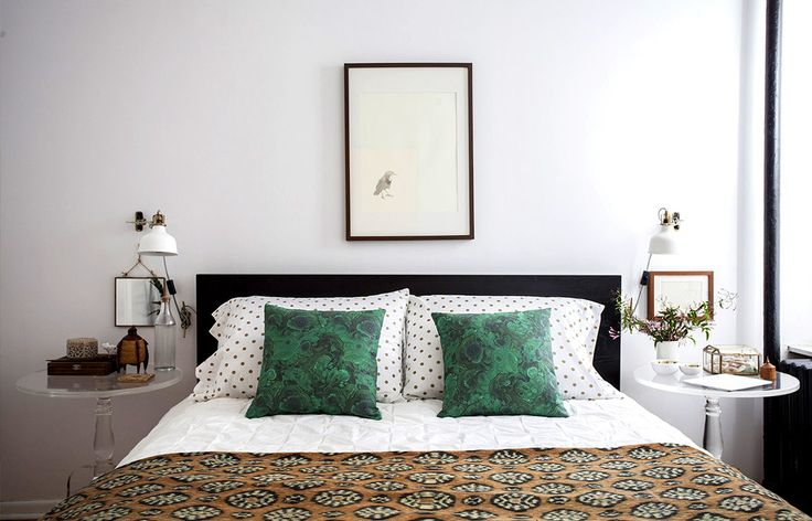 Eclectic bedroom with single art over bed, green pillows, matching side tables, and throw at foot of bed