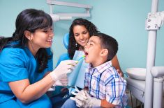 Hispanic dentist and mother teaching child use of toothbrush stock photo