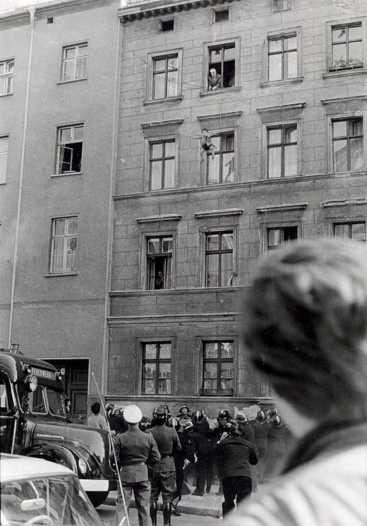 Four-year-old Michael Finder of East Germany is tossed by his father into a net held by firemen across the border in West Berlin. The apartments were in East Berlin while their windows opened into West Berlin (October 7, 1961). His mother and father also successfully jumped.