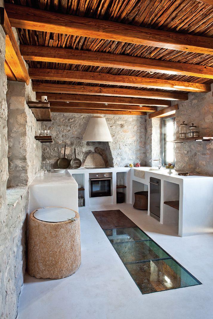 cocina rústica, con muebles de obra donde se integran los electrodomésticos, paredes de piedra, techos de madera, pavimento continuo, suelo de vidrio