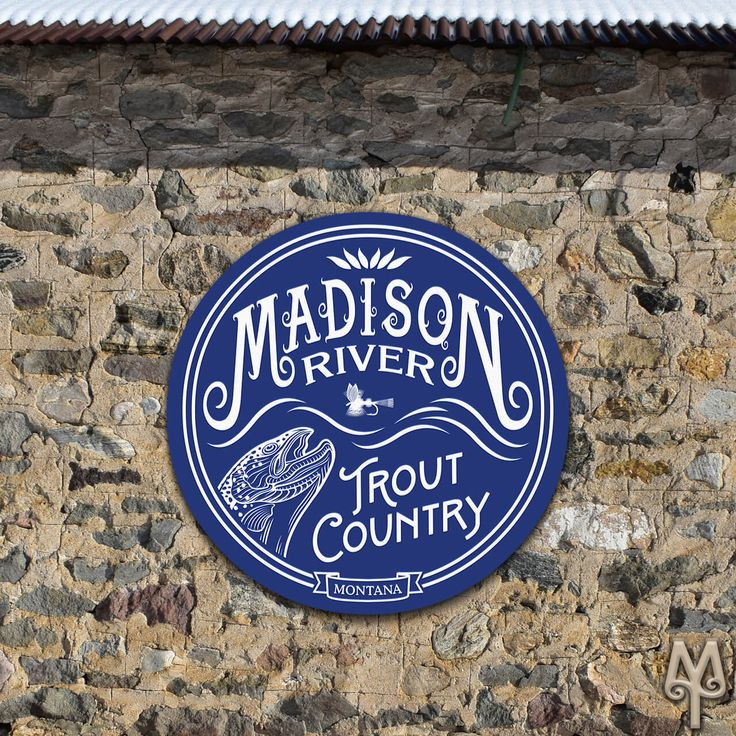 A New 28 inch diameter Madison River Trout Country wall sign hangs on the side of a building in historic Virginia City, Montana. Get one for yourself and display it in your home, cabin, or man-cave, today!