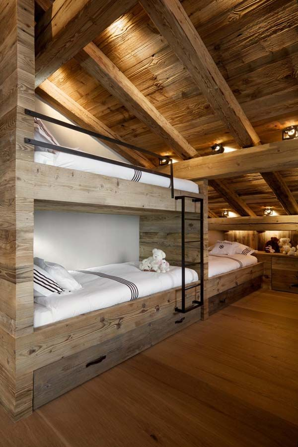 love the wood finish on the beds and use of the deep slope of the roof or A frame with 3 bunks, storage for blankets and pillow underneath and a desk and chair along the back wall