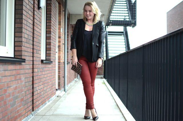 Zwart colbert met leren mouwen en rode gecoate broek