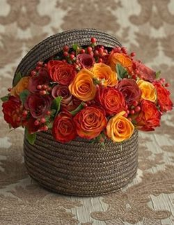 Beautiful autumn-hued roses in a tightly-woven basket