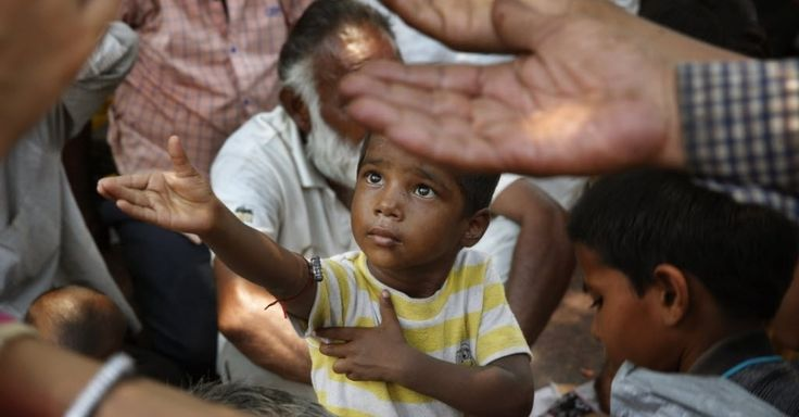 20150623 - Criança estende os braços para receber comida distribuída do lado de fora de um templo hindu, em Nova Déli, na Índia, nesta terça-feira (23). Um novo relatório da Unicef adverte que o crescimento econômico não está ajudando as crianças mais pobres do mundo. Na Índia, há inúmeras crianças que vivem em pobreza extrema  PICTURE: Manish Swarup/AP