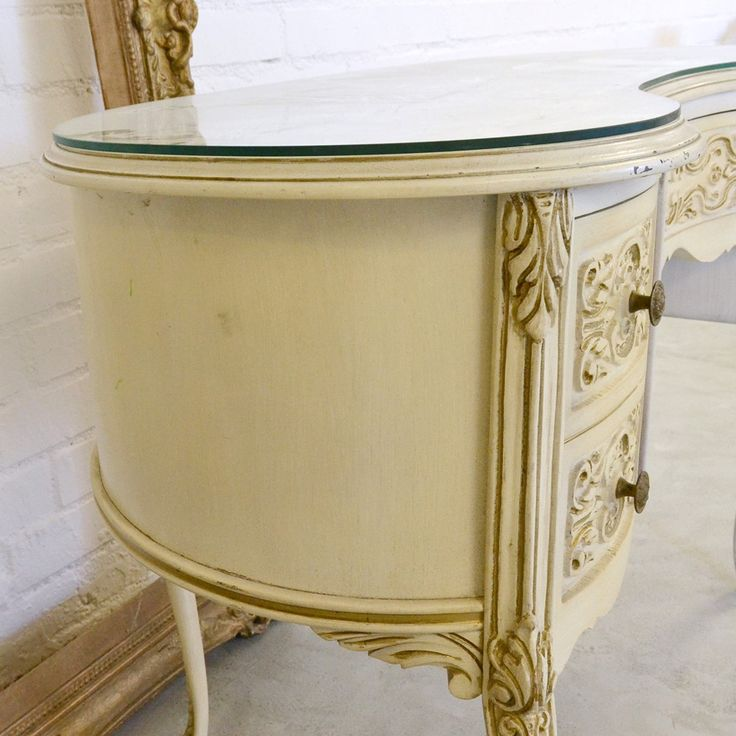 "In a unique kidney shape, this adorable desk is finished in cream with distressed details. The darling desk features one drawer on each side and one across the middle. Truly charming for any shabby chic style home. <BR><BR>  • Wood<BR> • Cream/Gold<BR> • 3 Drawers<BR> • 22""D x 42.5""W x 30""T<BR>"
