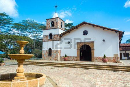Hermosa iglesia blanca en Mesa de los Santos en Santander Colombia con una fuente en el primer plano Foto de archivo