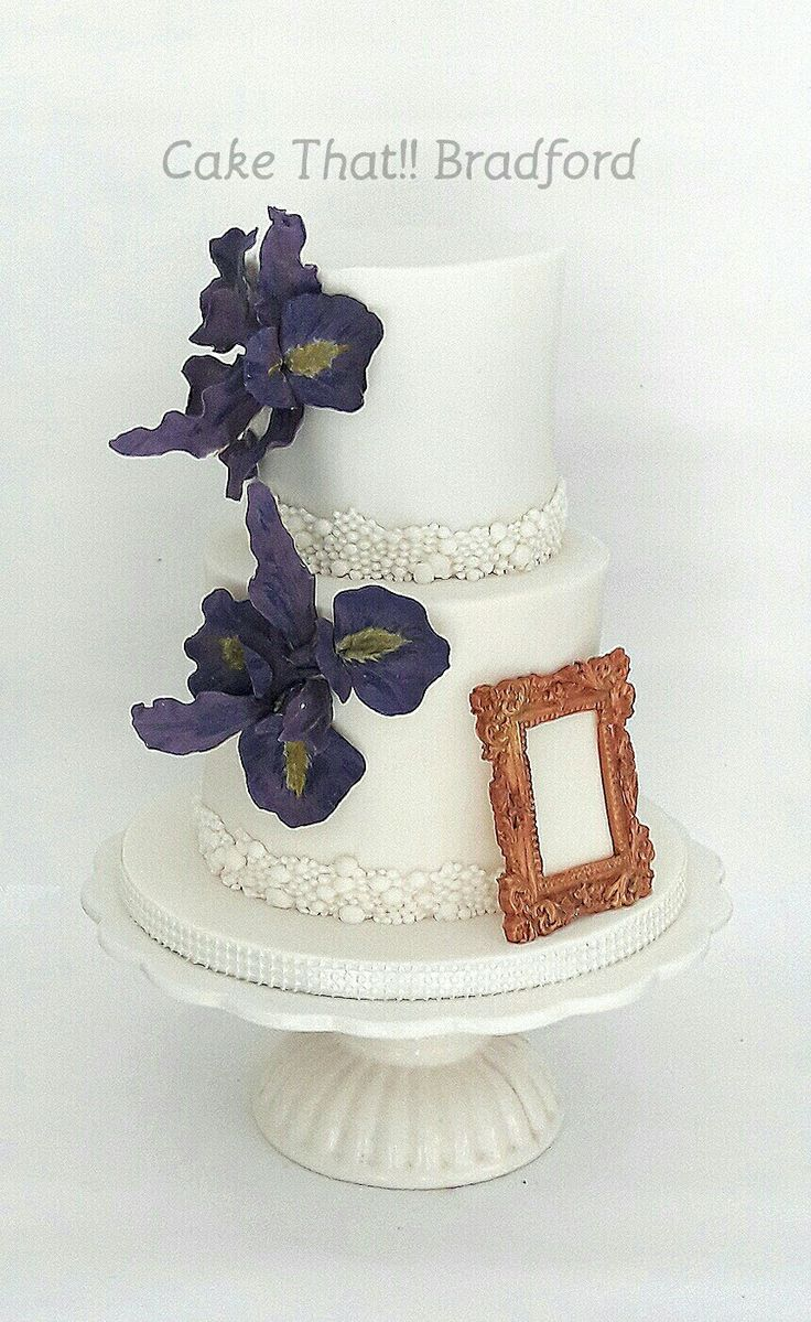 Ivory wedding cake with purple fondant iris flower. Gorgeous pearl cluster trim and a fondant gold photo frame