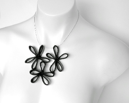 Rubber necklace. Unique, yet a classic style. Love it!  Three black free form flowers hang from plastic coated stainless steel wire finished with a magnetic clasp.