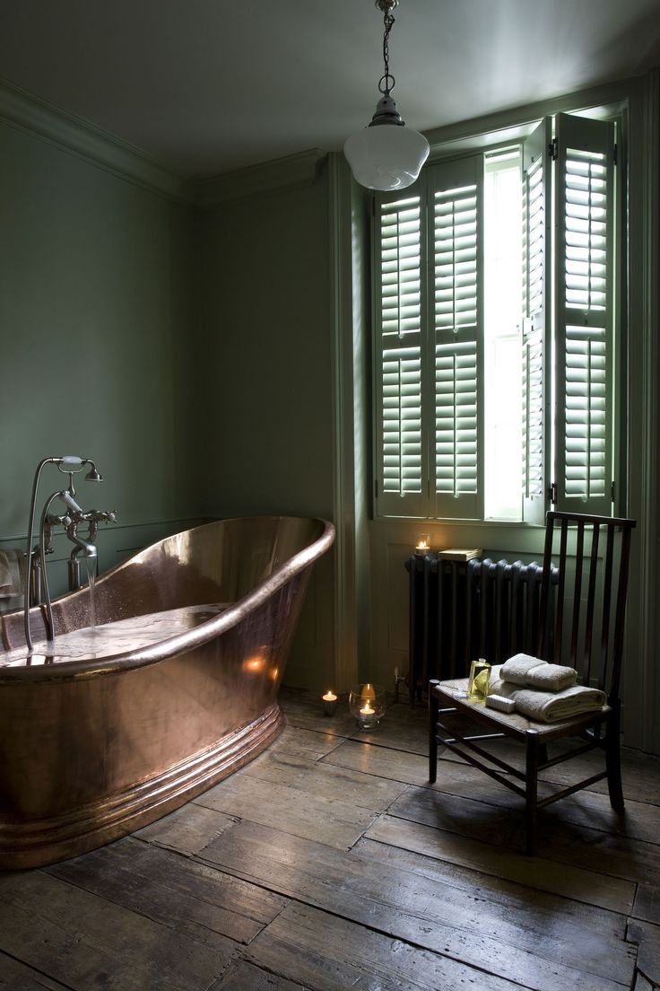 Pale green shutters add a vintage touch to this bathroom with antique copper bath. http://www.theshutterstore.com