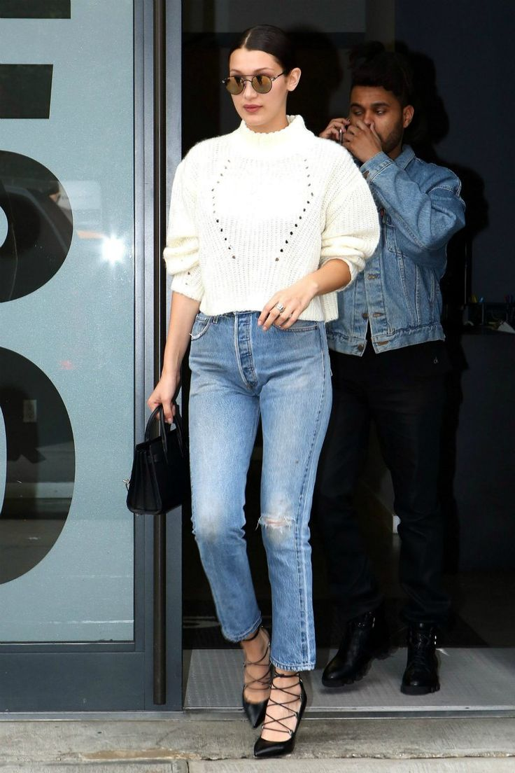 Bella Hadid in high waisted jeans, chunky white knit, and lace-up heels.