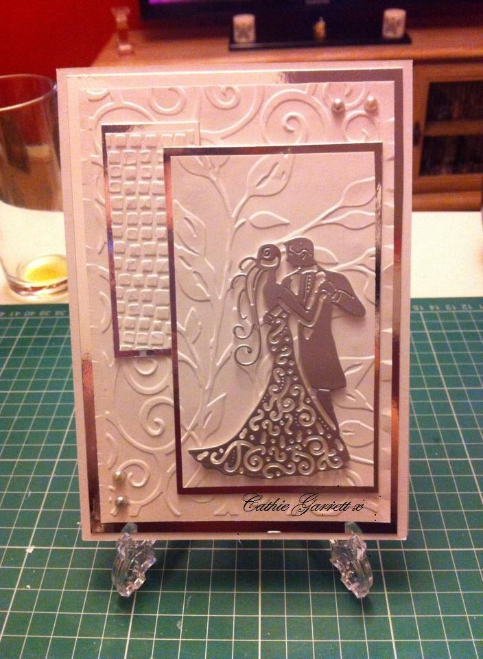 wedding card.. each panel has been embossed with a different pattern they were then layered on silver card.. the bride and groom is cut from  a tattered lace die..i added a few gems to give more sparkle..