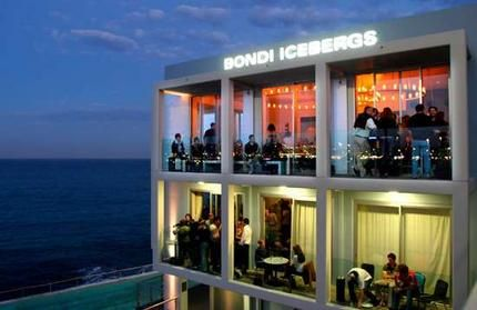 """Icebergs, Bondi Beach, New South Wales, Australia. """"On the hunt for hot, we came across this sweet spot right on the cusp of Aussie's fine coast. Since Australia isn't nearly as fickle as LA, we're pretty sure it's still swirling with sexy. Cliffside ocean views make Icebergs one of the most beautiful bars in the world. Have a seat on the outdoor patio right up against the water or lounge on plush couches inside, where floor-to-ceiling glass windows & candlelight showcase pristine views."""""""