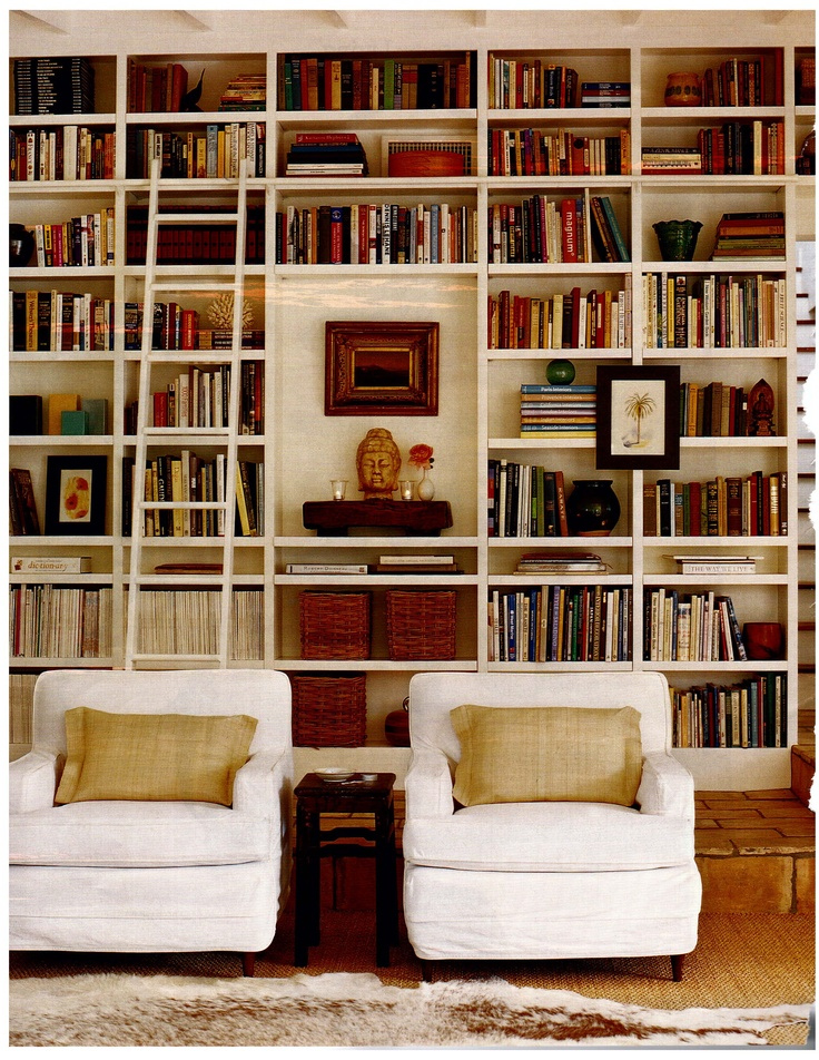 light library space with lovely white armchairs and floor to ceiling bookshelves artfully stocked floor to ceiling bookshelves with ladder