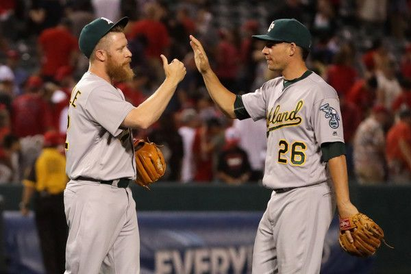 Danny Valencia Photos - Sean Doolittle #62 is congratulated by Danny Valencia #26 of the Oakland Athletics during the ninth  inning of a baseball game against the Los Angeles Angels of Anaheim at Angel Stadium of Anaheim on June 23, 2016 in Anaheim, California. - Oakland Athletics v Los Angeles Angels of Anaheim