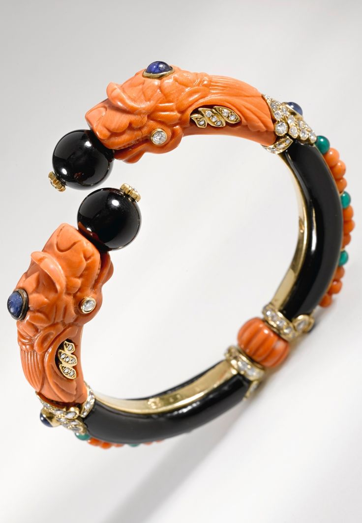 Van Cleef & Arpels - An Art Deco coral, onyx, sapphire and diamond bangle, circa 1925. Designed as opposing dragons heads composed of carved coral decorated with onyx beads, cabochon sapphires, circular- and single-cut diamonds, the swivelling bangle of carved onyx, decorated with cabochon sapphires, circular-cut and single-cut diamonds, chalcedony and coral beads, signed V.C.&A., numbered. #VanCleefArpels #ArtDeco #bangle