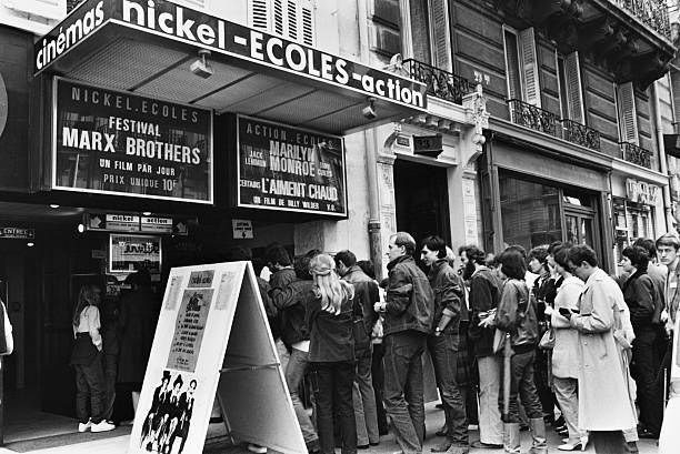 Cinemagoers queue outside the Nickel Écoles cinema a cinema specialising in old American films Paris France July 1980