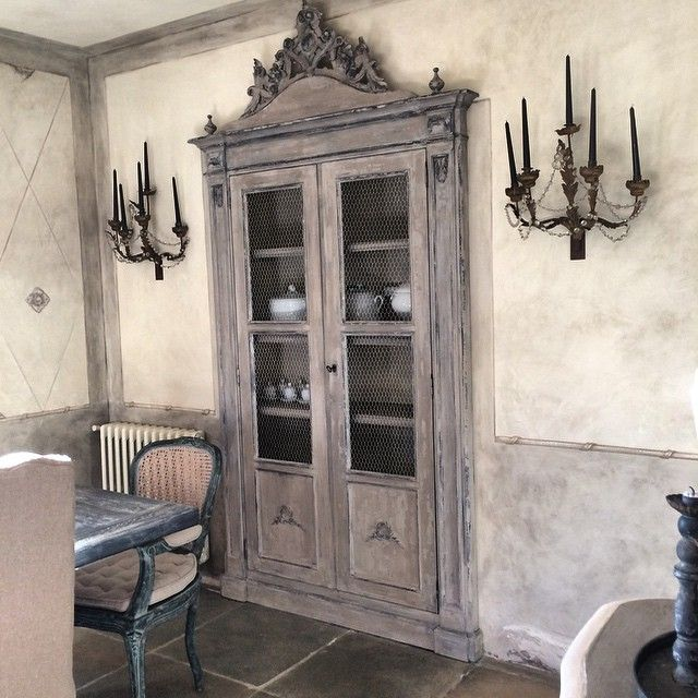 Between the studs!  I see 2 beautiful old doors, wire windows, molding, narrow shelves between studs