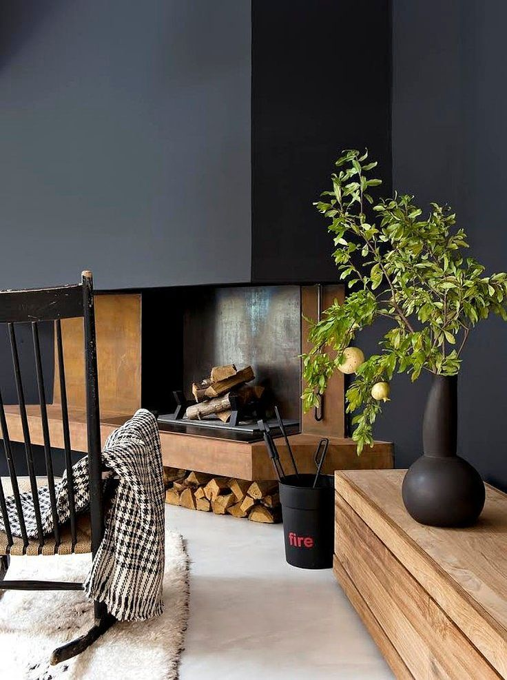 .Black walls over wooden fireplace Juxtaposition of fireplace and bench