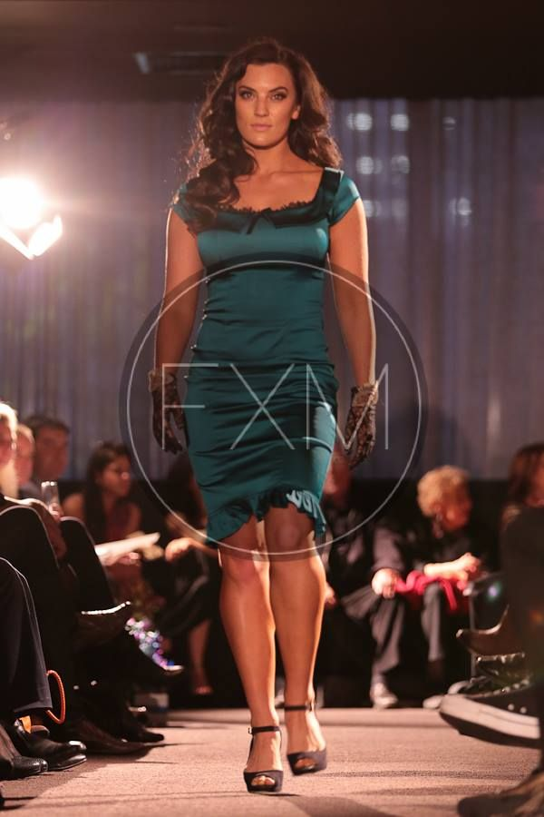 High Tea Dress- Emerald green deluxe satin dress with paneling that accentuates curves in a glamourous and sleek 50s silhouette.  Accented with delicate scallop lace edging and slim black velvet bow trimmed at bust line. Elegant knee length with a sweet ruffle trim.