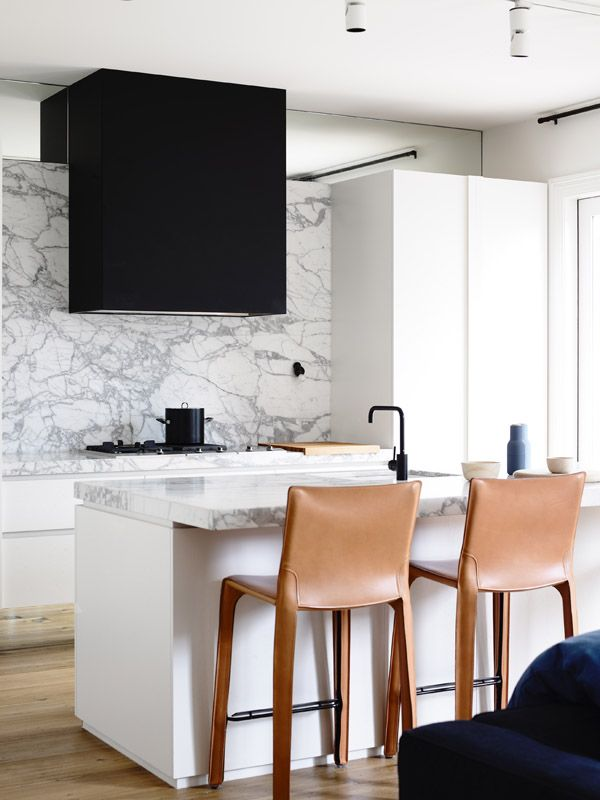 white kitchen + black range hood + marble counter + backsplash + leather wrapped chairs