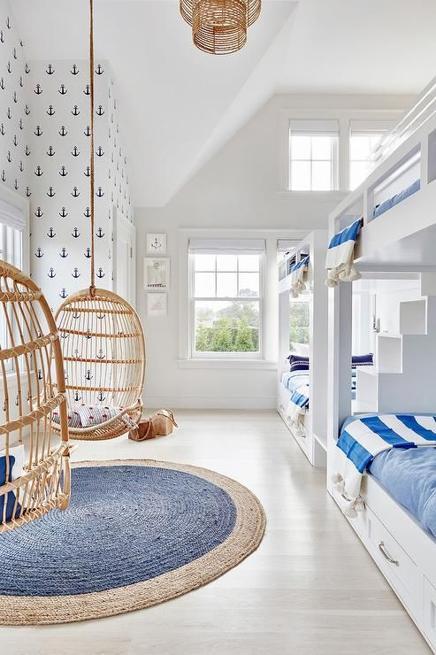 White and blue boys' bunk room featuring two sets of white built-in bunk beds dressed in white and blue bedding as well as blue awning stripe throw blankets flanking a built-in staircase.