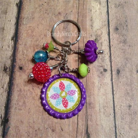 Check out this stylish flower keychain!   This key chain is approximately 3 3/8 long.   It is made of a flattened bottle cap and embellished with cute beads.   *Purple flattened bottle cap, colored on both sides   *Clear epoxy sticker over image   *Acrylic and resin dangle beads   *Please Note*   We try our hardest to take photos in the best light possible. Therefore, colors may slightly vary due to camera/device settings and monitor resolutions.   If you have any questions about th...