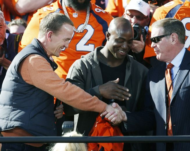 Denver Broncos quarterback Peyton Manning, left, shakes hands with radio announcer Dave Logan, right, as linebacker DeMarcus Ware looks on at a rally