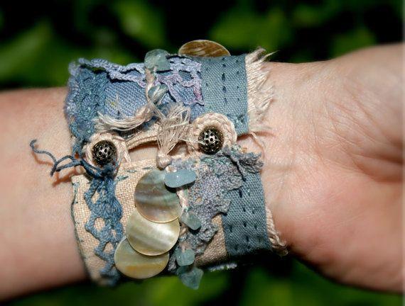 Jai fait ce bracelet manchette de Bohème textile avec des couches de toile de lin, dentelle vintage et le crochet.  Il est orné de magnifiques perles aigue-marine bleus, les trois dans le centre sont assez volumineux et fil sur un fil dargent sterling. Les perles aigue-marine puce sont tressés avec ficelle de linge. Pour une beauté supplémentaire jai cousu quelques boutons de nacre sur le bracelet.  Les couleurs sont Ivoire, beige et bleu de mauvaise humeur.  Sur le tissu de la doublure il…