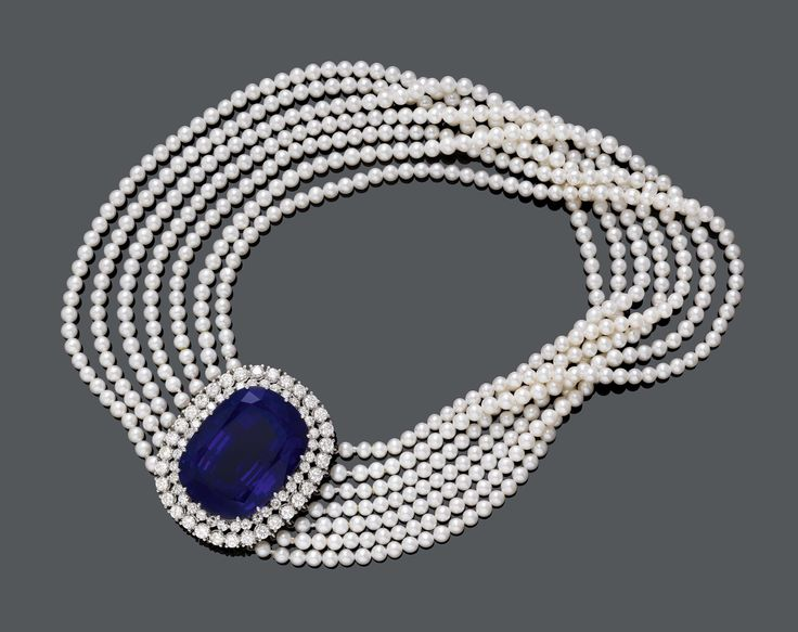TANZANITE, DIAMOND AND PEARL CHOKER. White gold 750. Very fancy, seven-row necklace of numerous Akoya pearls of 4 mm Ø, with an elegant clasp in the centre, set with 1 antique-oval tanzanite weighing ca. 136.36 ct, within a double-border of 52 brilliant-cut diamonds weighing ca. 13.20 ct l. L ca. 34.5 cm.