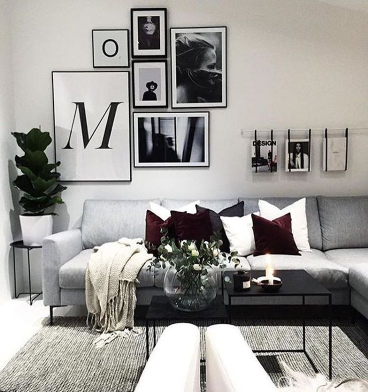 Cute white scandinavian home with black and white living room with burberry details. Photo wall contains framed posters from printler.com, the marketplace for photo art.