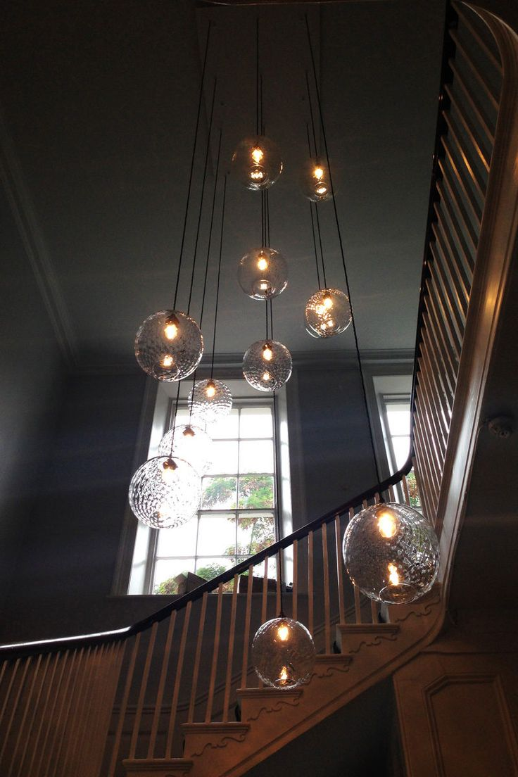Twelve clear round lights hanging in a period home stairway