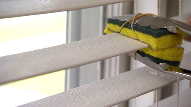 Use this tip to clean blinds easily. Clean blinds easily using kitchen tongs and a sponge. Cut the sponge in half and attach it to the tongs using rubber bands. Dip the tongs in warm water and clean both sides of the slat at once.