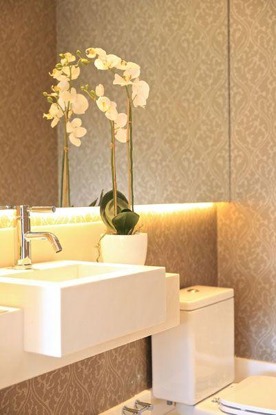 Este lavabo projetado pela designer de interiores Marcia Brunello tem paredes revestidas com papel de parede, cuba em mármore sivec e luzes de led abaixo do espelho, peças que proporcionam um clima intimista e sofisticado no ambiente.