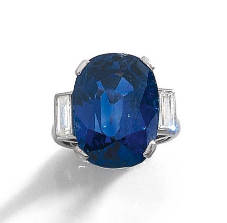 BAGUE <br>en platine, ornée d'un beau saphir ovale pesant 19,46 cts, épaulé de deux diamants baguettes sertis clos. <br>Vers 1930. <br>Dimensions de la pierre : 17,20 x 12,60 x 9,20 mm. <br>Poids : 11,1 g. (anneau interne) <br>A diamond and platinum ring set with an oval shaped sapphire weighing 19,46 cts, circa 1930. <br>La pierre accompagnée d'un certificat Carat Gem Lab attestant : origine Birmanie (Burma), couleur naturelle sans ...