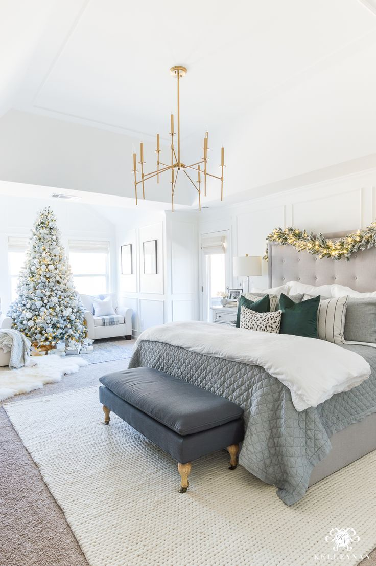 Gray and white Christmas bedroom with a pop of green and modern chandelier #masterbedroomdecor #bedroomdesign #christmasbedroom #graybed