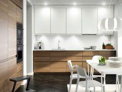 Cocina con puertas efecto nogal, puertas blancas y encimera también blanca. acabada con un extractor de acero inoxidable, un horno microondas y un horno gris oscuro.