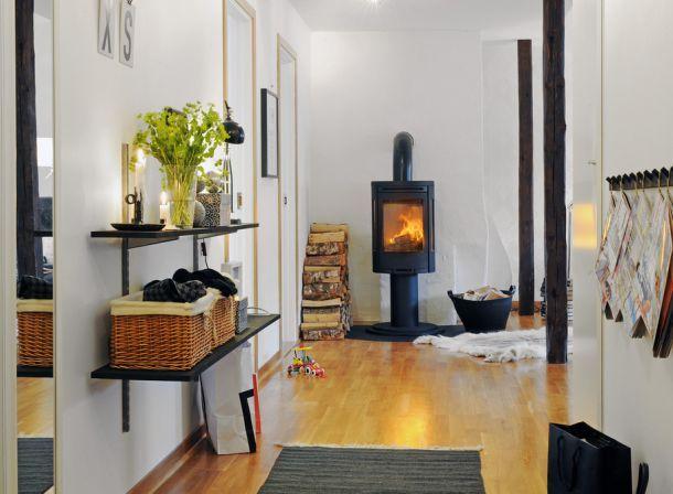 czarny mały kominek,żeliwny kominek,czarne meble,wąski przedpokój,biały przedpokój,korytarz,jak urzadzić wąski korytarz,biale ściany,skandynawski styl,nowoczesne mieszkanie,dekoracja holu,dekoracje do przedpokoju,typografie,czarny chodnik,dywan w przedpokoju,biała podłoga