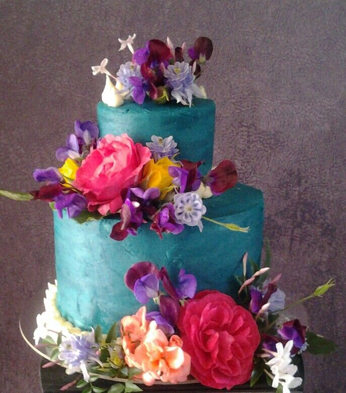 Yummy vanilla berry cake with buttercream icing and beautiful fresh garden flowers.