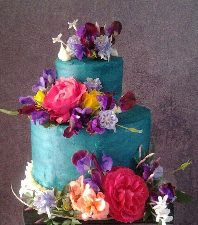 Yummy vanilla berry cake with buttercream icing and beautiful fresh garden flowers.