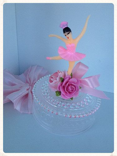 Een mooie Snuisterijdoosje heeft een dansende ballerina op de top. Het heeft zijn verfraaid met papieren bloemen en een kleine roze strik. Er is ruimte binnen voor snoep of andere kleine gunsten. Indien u wenst, kan ik een naam toevoegen.  ongeveer 3 1/2 inch hoog  Ziet er geweldig versieren een dessert tafel in de partij van de verjaardag van een ballerina.